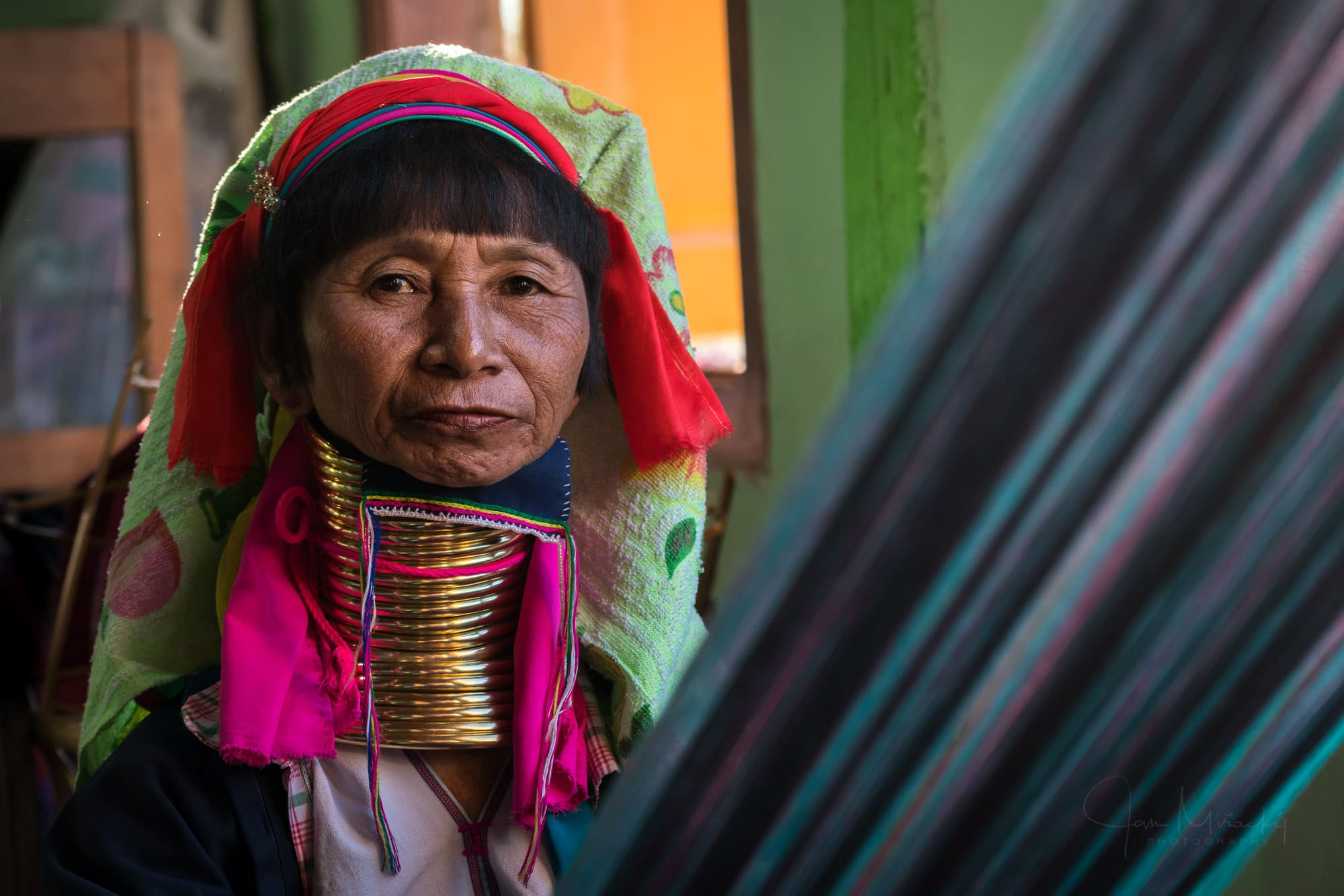 Old woman from Kayan (Long-neck) tribe in weaving workshop