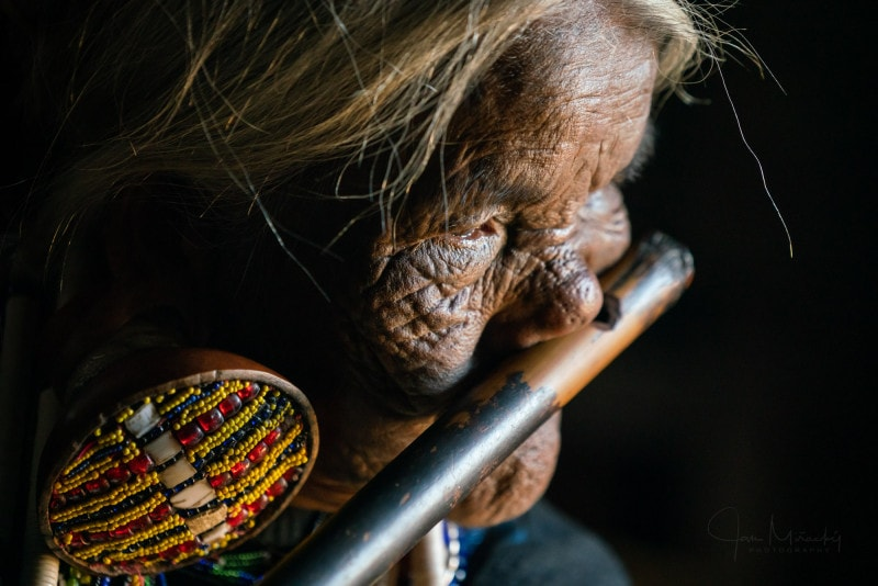 Woman playing nose-flute in Chin State, Myanmar